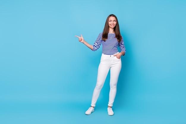 Vue sur toute la longueur de la taille du corps d'elle, elle, jolie fille gaie et attrayante, démontrant une publicité, une copie de l'annonce, un espace vide vide, un endroit isolé, un fond de couleur bleu vif, brillant et éclatant