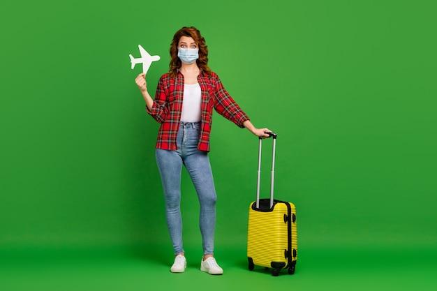 Vue sur toute la longueur de la taille du corps d'elle, jolie fille aux cheveux ondulés au gingembre foxy portant un masque de gaze tenant dans un avion en papier à la main isolé sur fond de couleur vert vif et brillant