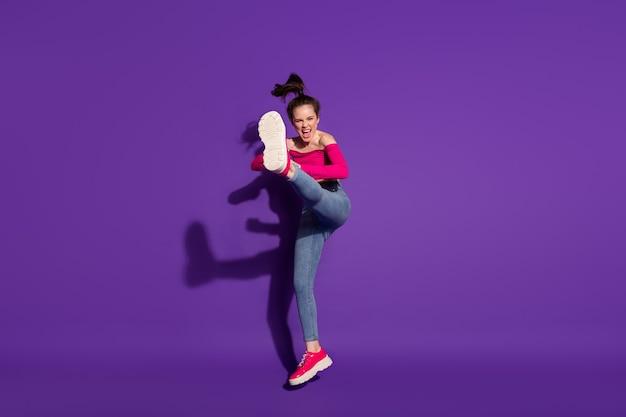 Vue sur toute la longueur de la taille du corps d'une fille gaie forte combattant l'art du judo ennemi invisible isolé sur fond de couleur violet vif