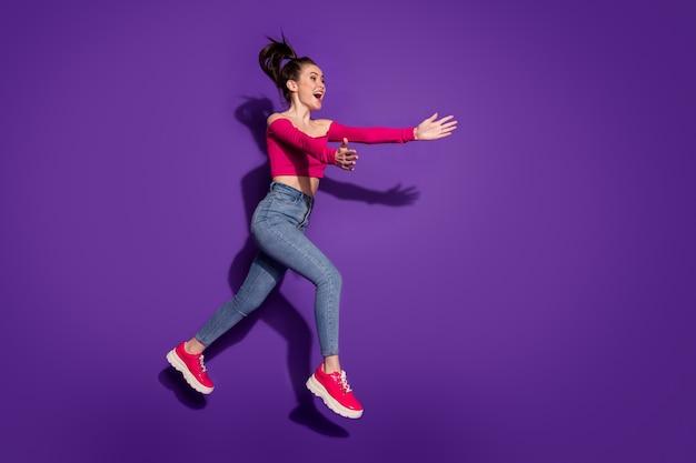 Vue sur toute la longueur de la taille du corps d'une fille gaie et mince sautant en courant étreignant des personnes invisibles isolées sur fond de couleur violet vif