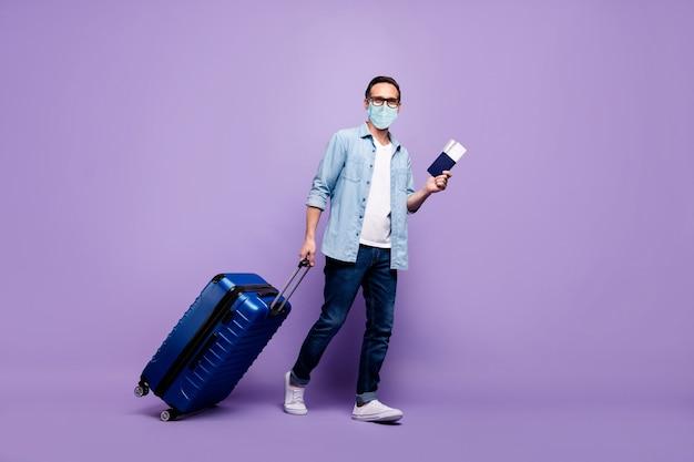 Vue sur toute la longueur de la taille du corps d'un homme mûr tenir un gros billet de bagage arriver à l'étranger enregistrement portant un masque de gaze sûr cov mers 2019-ncov prévention chine wuhan isolé violet violet fond de couleur lilas