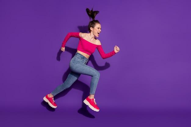 Vue sur toute la longueur de la taille du corps d'une jolie fille folle et déterminée sautant active isolée sur fond de couleur violet vif