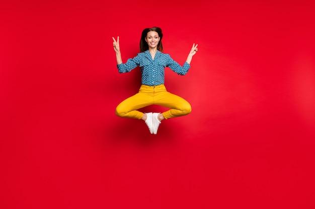 Vue sur toute la longueur de la taille du corps d'une jolie fille gaie sautant assis pose de lotus montrant v-sign isolé fond de couleur rouge vif