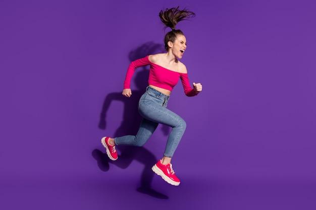 Vue sur toute la longueur de la taille du corps d'une jolie fille joyeuse et déterminée sautant en cours d'exécution sur fond de couleur violet vif isolé