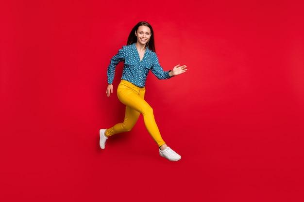 Vue sur toute la longueur de la taille du corps d'une jolie fille joyeuse en forme sautant en cours d'exécution de mouvement actif isolé sur fond de couleur rouge vif