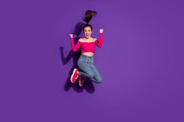 Vue sur toute la longueur de la taille du corps d'une jolie fille joyeuse et joyeuse sautant de joie isolée sur fond de couleur violet vif