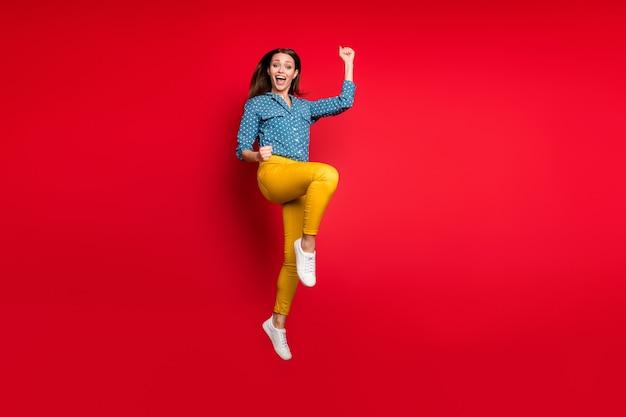 Vue sur toute la longueur de la taille du corps d'une jolie fille joyeuse sautant se réjouissant de bonnes nouvelles isolées sur fond de couleur rouge vif