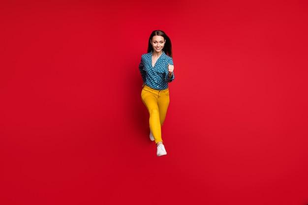 Vue sur toute la longueur de la taille du corps d'une jolie fille mince et joyeuse sautant en mouvement isolé sur fond de couleur rouge vif