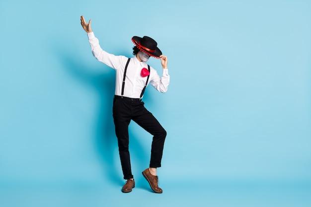 Vue sur toute la longueur de la taille du corps de son mystérieux homme maigre et grand étranger dansant s'amusant à se cacher le visage derrière le culte rituel du sombrero isolé sur fond de couleur bleu vif brillant éclatant