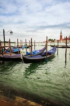 Vue traditionnelle de san marco, venise, italie. gondoles bleues garées sur canal grande, église san giorgio maggiore à l'arrière-plan