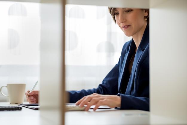 Vue à travers la cloison de bureau en bois d'une jeune femme d'affaires utilisant une calculatrice et lisant des documents.