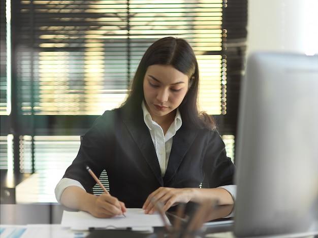Vue à travers le mur de verre de femme d'affaires travaillant dans la salle de bureau
