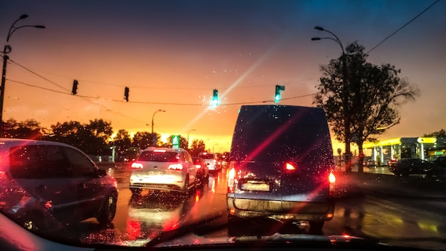 Vue à travers le pare-brise de la route mouillée après la pluie au coucher du soleil