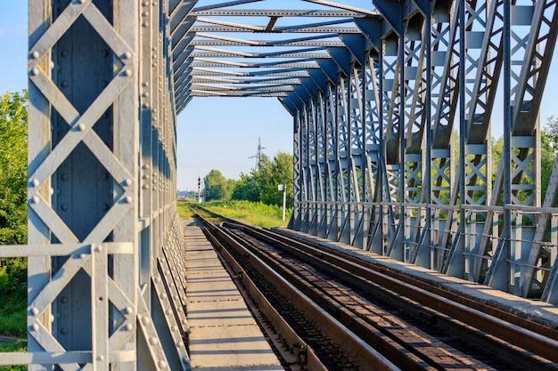 Vue à travers le pont de chemin de fer dans la campagne au matin ensoleillé