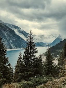 Vue à travers les sapins sur le lac de montagne turquoise clair de schlegays couvert de nuages et de brouillard. alpes de zillertal, mayrhofen, autriche.