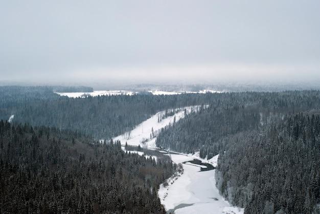 Une vue sur la vallée d'hiver d'une rivière gelée au milieu de collines boisées enneigées vue de dessus