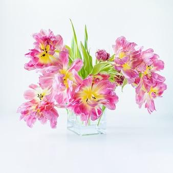Vue d'un vase rectangulaire en verre avec un bouquet de tulipes roses sur fond blanc. fond de concept, fleurs, vacances