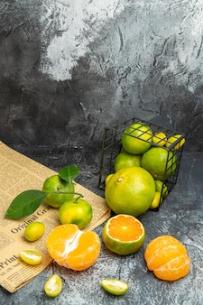 Vue verticale d'agrumes frais avec des feuilles tombées d'un panier noir coupé en deux formes sur papier journal sur fond gris