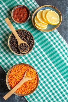 Vue verticale de l'arrière-plan du dîner avec différentes épices pois jaune sur une serviette verte sur une table sombre