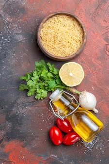 Vue verticale de l'arrière-plan du dîner pâtes non cuites citron un tas de vert bouteille d'huile sur fond sombre