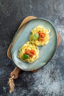 Vue verticale d'une assiette bleue avec un délicieux repas de pâtes servi avec de la tomate et de la viande sur une planche à découper sur une table sombre