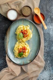 Vue verticale d'une assiette bleue avec un délicieux repas de pâtes servi avec de la tomate et de la viande sur une serviette de couleur beige pour le dîner différentes épices