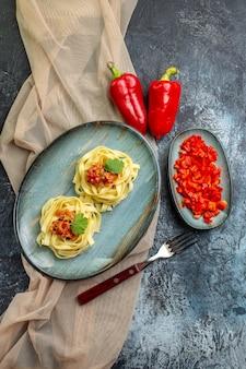 Vue verticale d'une assiette bleue avec un délicieux repas de pâtes servi avec de la tomate et de la viande sur une serviette de couleur beige pour le dîner ses ingrédients