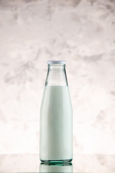 Vue verticale de la bouteille en verre de lait fermée et remplie sur fond de fumée blanche avec espace libre