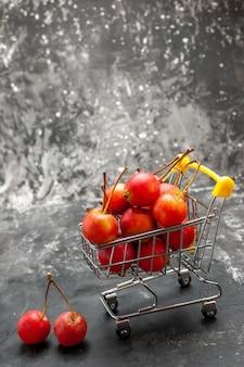 Vue verticale des cerises rouges à l'intérieur et à l'extérieur du mini-tableau commercial avec sur gris
