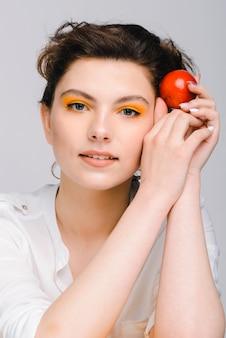 La vue verticale de la dame caucasienne regarde la caméra avec un léger sourire tout en tenant une prune rouge près de son visage. concept d'apparence de personnes