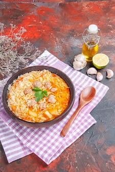 Vue verticale d'une délicieuse soupe au poulet avec des nouilles vertes et une cuillère sur une bouteille d'huile de serviette dénudée rose citron à l'ail sur fond sombre