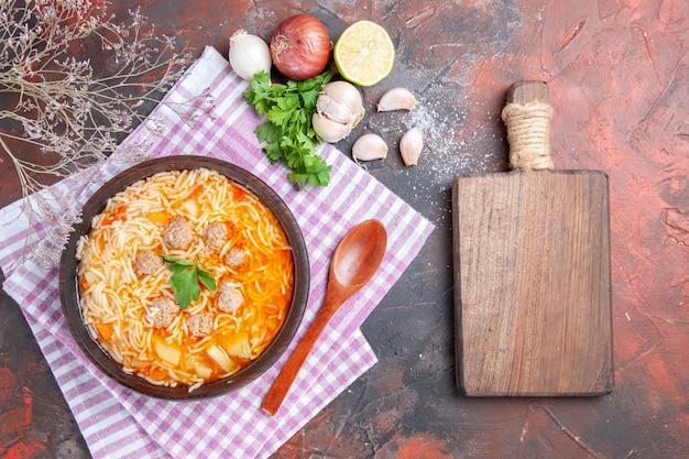 Vue verticale d'une délicieuse soupe au poulet avec des nouilles vertes et une cuillère sur une bouteille d'huile de serviette dénudée rose citron ail et planche à découper sur fond sombre