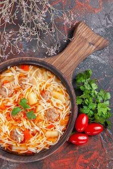 Vue verticale d'une délicieuse soupe de nouilles au poulet sur une planche à découper en bois un tas de tomates vertes sur une table sombre