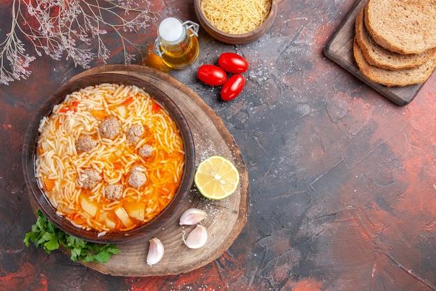 Vue verticale d'une délicieuse soupe de nouilles avec du poulet sur une bouteille d'huile de tary greens en bois, des tomates au citron à l'ail et des tranches de pain sur fond sombre