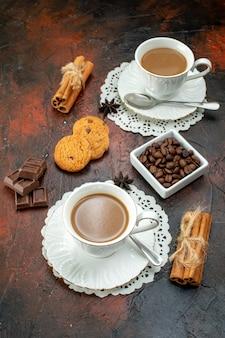 Vue verticale d'un délicieux café dans des tasses blanches sur des serviettes, des biscuits, des barres de chocolat à la cannelle et au citron vert sur fond de couleur mélangée