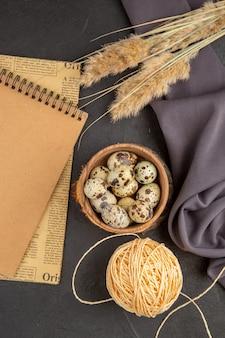 Vue verticale de divers œufs biologiques dans une serviette noire en pointe de corde de pot marron sur fond sombre
