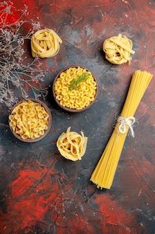 Vue verticale de divers types de pâtes non cuites sur fond de couleur mixte