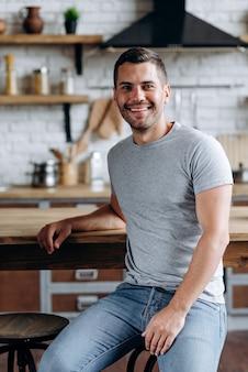 Vue verticale du bel homme assis sur la chaise s'est penché sur la table, souriant et regardant la caméra. image à la cuisine confortable