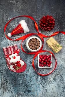 Vue verticale du chapeau de père noël et du cadeau de cône de conifère rouge de chaussette de nouvel an de chocolat de cornel sur la surface foncée