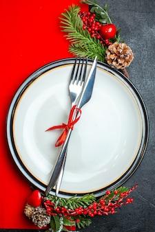 Vue verticale du fond de noël avec des couverts sertie de ruban rouge sur une assiette à dîner accessoires de décoration branches de sapin sur une serviette rouge