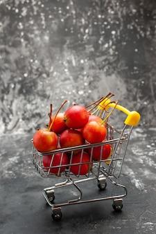 Vue verticale du mini tableau commercial avec des cerises rouges sur fond gris