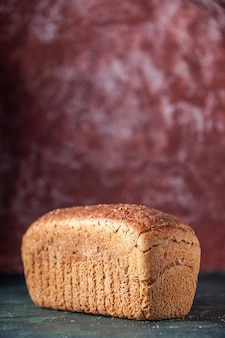 Vue verticale du pain noir emballé sur fond marron en détresse avec espace libre