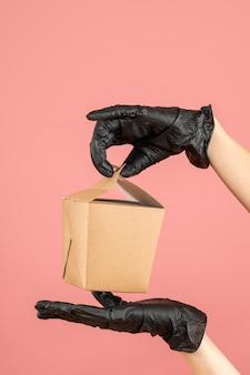Vue verticale du port d'un gant noir ouvrant à la main une petite boîte sur une pêche pastel