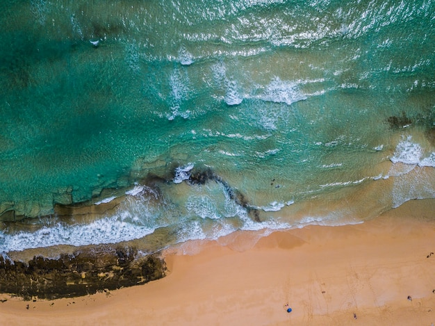 Vue verticale de l'eau de mer bleue et propre et de la plage de sable jaune - concept de lieu pittoresque tropical.et vacances d'été - tourisme et touristes