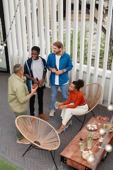 Vue verticale en grand angle sur un groupe diversifié de jeunes profitant d'une fête en plein air sur le toit, espace pour copie