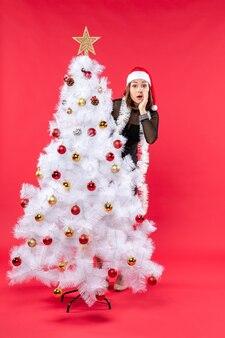 Vue verticale de l'humeur du nouvel an avec belle fille dans une robe noire avec chapeau de père noël se cachant derrière l'arbre de noël