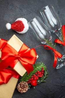 Vue verticale de l'humeur de noël avec de beaux cadeaux avec ruban en forme d'arc et branches de sapin accessoires de décoration chapeau de père noël gobelets en verre tombé cônes de conifères sur fond sombre