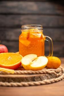 Vue verticale de jus de fruits frais bio dans une bouteille servie avec tube et fruits sur une planche à découper et sur une table en bois marron
