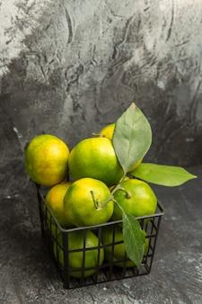 Vue verticale de mandarines vertes fraîches avec des feuilles dans un panier sur fond gris