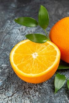Vue verticale de l'orange fraîche coupée en deux et entière avec des feuilles sur fond gris photo stock